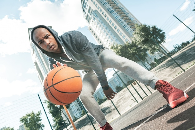 스포츠 훈련. 농구 훈련을하는 동안 운동장에 오는 즐거운 젊은 남자