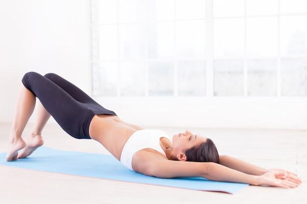 Спортивная подготовка. вид сбоку красивой молодой индийской женщины, тренирующейся на коврике для йоги