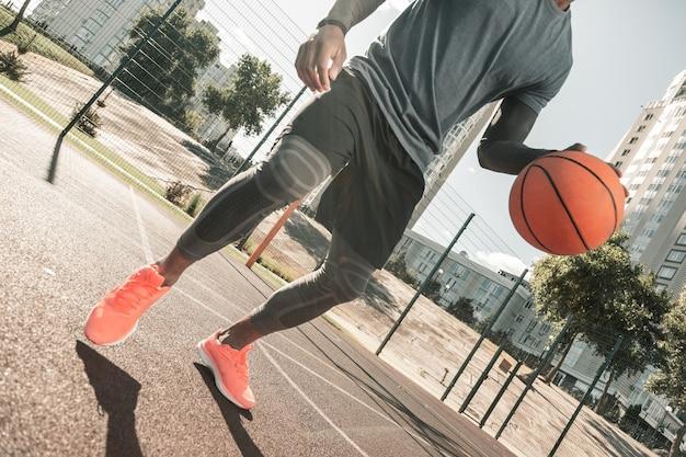 スポーツトレーニング。スポーツトレーニングをしながらバスケットボールをしているよく造られたいい男