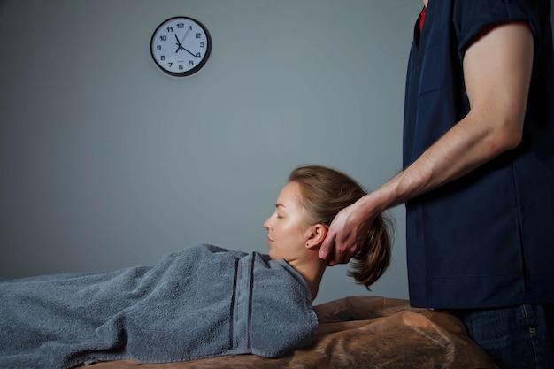 フィットネスジムの医療室でのスポーツウェルネスマッサージ。マッサージ師はマッサージの練習をします。スポーツボディの治療再生マッサージ。スポーツ傷害のリハビリテーションの概念。コピースペース