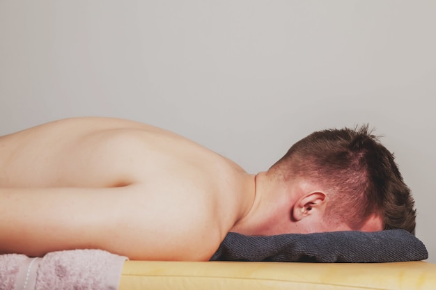 フィットネスジムの医療室でのスポーツウェルネスマッサージ。マッサージ師を待っているソファの上の患者。スポーツボディの治療再生マッサージ。スポーツ傷害のリハビリテーションの概念。コピースペース