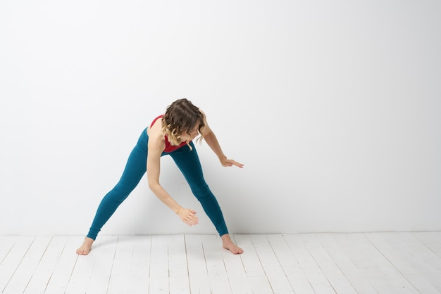 Sports woman in a bright room doing yoga in full growth blue leggings and a red tank top
