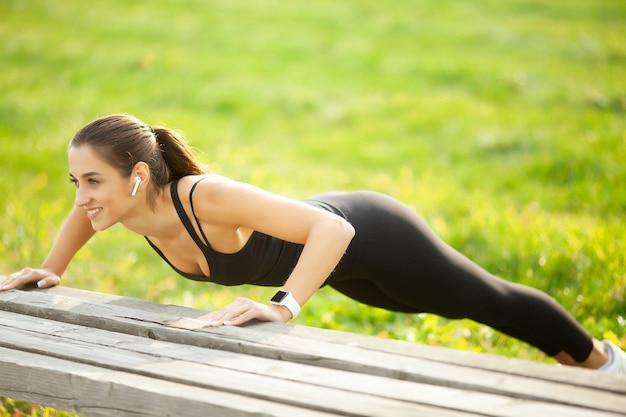 Sports woman doing exercises on bench and listening to music in the urban environment