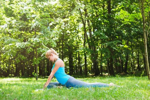 Спортивная женщина занимается йогой на открытом воздухе