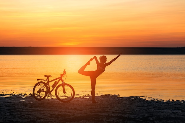 The sports woman doing yoga at sunrise on the sea beach