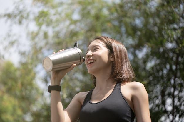 スポーツの女性はステンレス鋼ブレンダーボトルシェーカーからプロテインシェイクを飲みます