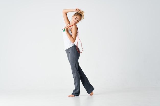 縄跳びフィットネスライトの背景で運動するスポーツの女性。高品質の写真