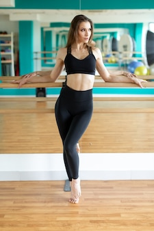 Sports woman in fashion sport clothes stretching body.
