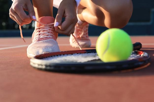 야외에서 신발끈을 묶는 테니스를 칠 준비를 하는 스포츠 여성.