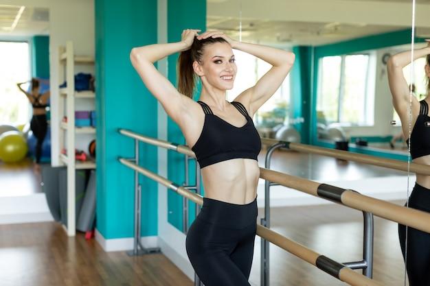 Спортивная женщина в модной спортивной одежде протягивая тело.