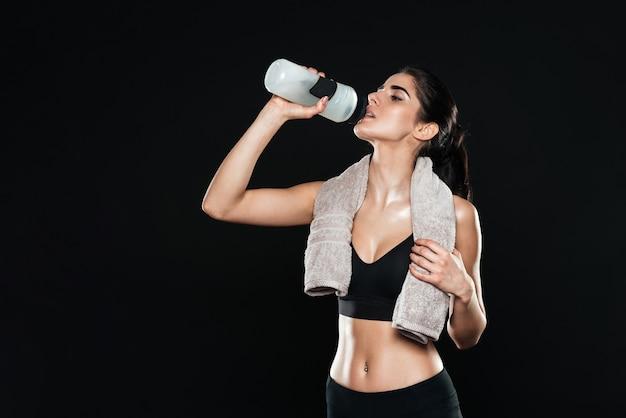 Спортивная женщина в тренажерном зале стоит над черной стеной с питьевой водой и держит полотенце