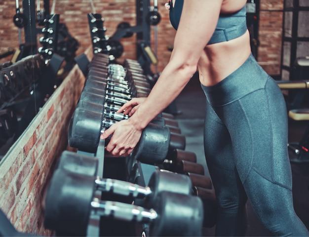 Спортивная женщина в спортивной одежде берет гантели со стойки