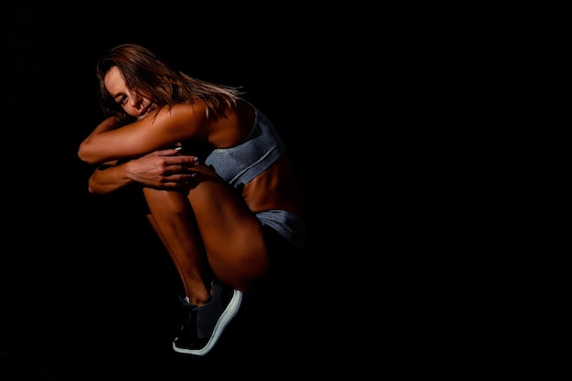 暗闇の上に黒いスポーツウェアを着ているスポーツの女性の肖像画。黒の背景にポーズをとるセクシーなフィットの女性。