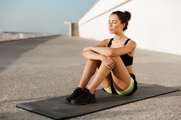 ビーチで屋外の敷物の上に座っているスポーツの女性。