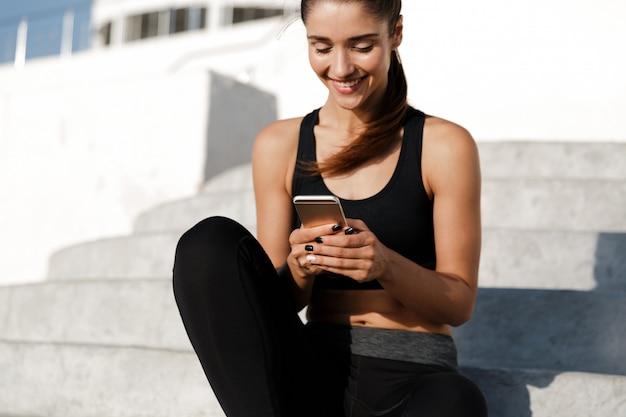 屋外の電話でチャットの手順の上に座ってスポーツ女性。