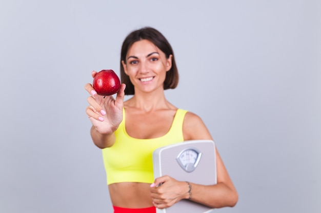 Sports woman stands on gray wall, satisfied with the results of fitness training and diet, holding scale, wears top and leggings, holds apple