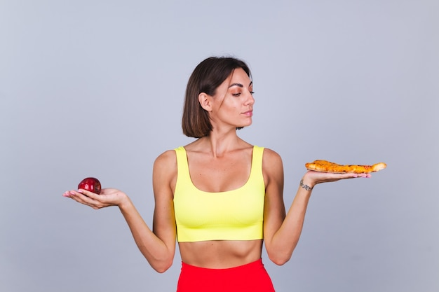 Sports woman stands on gray wall, satisfied with the results of fitness training and diet, holds apple and pizza in hands thoughtful