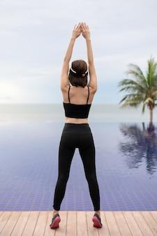 Спортивная женщина растягивается и готовится к бегу у бассейна по утрам.