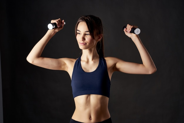 Sports woman with dumbbells in hands workout fitness dark background. high quality photo