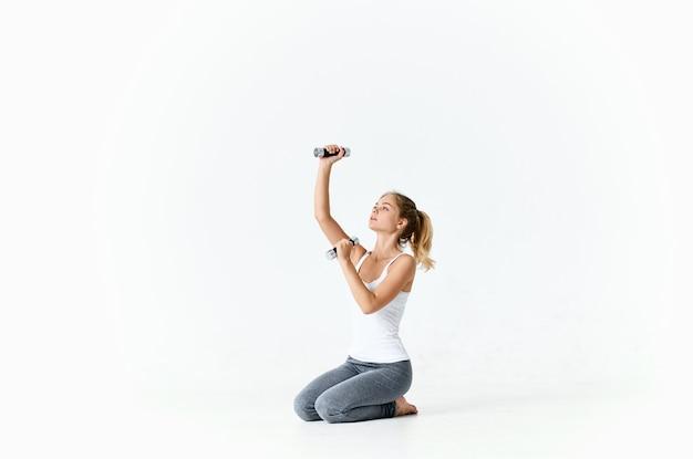 手にダンベルを持つスポーツの女性のモチベーショントレーニング
