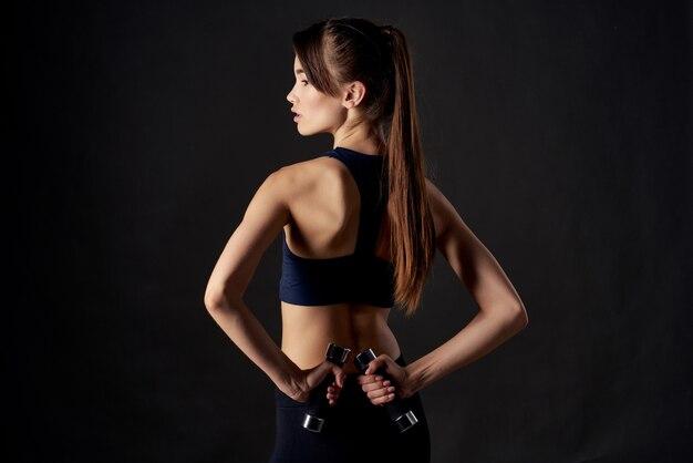 手トレーニングフィットネス暗い背景にダンベルを持つスポーツの女性