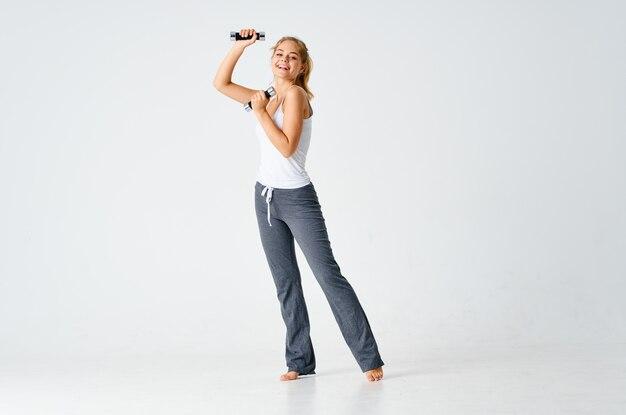 手トレーニングライトフィットネスの背景にダンベルを持つスポーツの女性