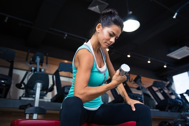 Sports woman workout with dumbbell on the bench in gym