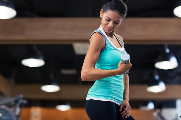 Sports woman workout with dumbbells in fitness gym