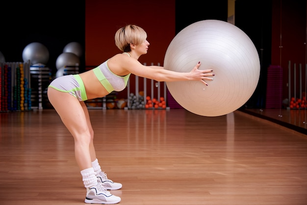 Sports young woman is training in the gym.