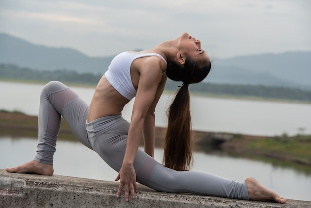 Sports young women practicing yoga in the morning by the reservoir with mountains background.