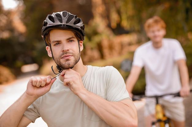 자전거 타기 전에 헬멧 끈을 조정하는 스포츠맨