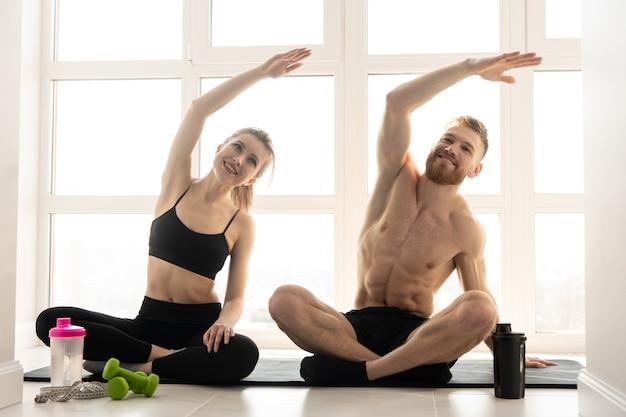 フィットネスマットで運動をしているスポーツマンとスポーツウーマン。金髪の女性はスポーツウェアを着用します。裸の胴体を持つひげを生やした男。家庭でのスポーツ活動の概念。広々とした日当たりの良いアパートのインテリア