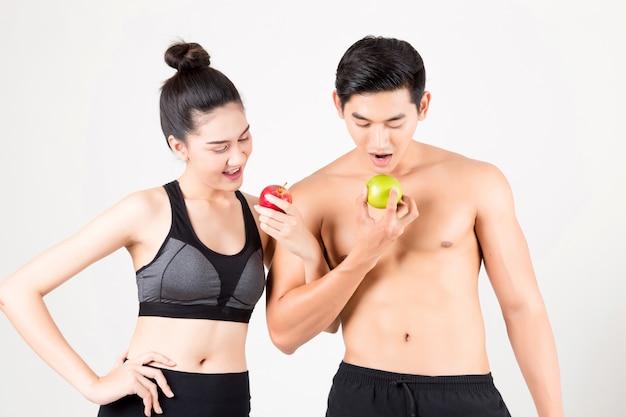 スポーツマンとスポーツウーマンが赤と緑のリンゴを食べる