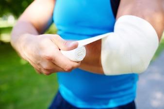 Sportsman bandaging the elbow