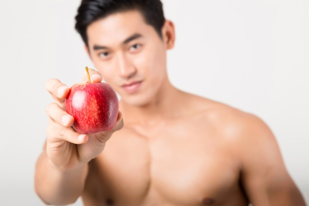 Sportsman bites green apple after training. fitness and healthy lifestyle concept. studio shot on white background.