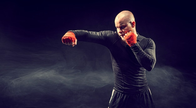 Sportsman boxer fighting on black background with smoke boxing