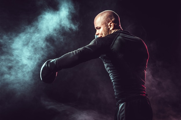 Sportsman boxer fighting, hitting side impact on black space with smoke