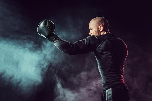 Sportsman boxer fighting, hitting uppercut on black space with smoke