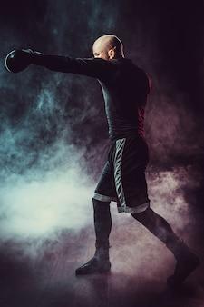 연기와 함께 검은 공간에 싸우는 스포츠맨 권투 선수