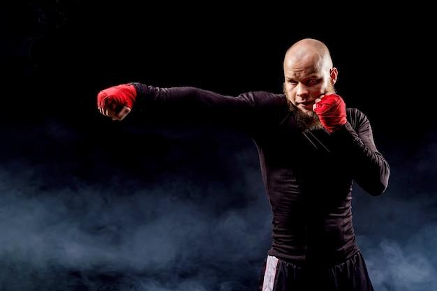 Спортсмен боксер борется на черном пространстве с дымом