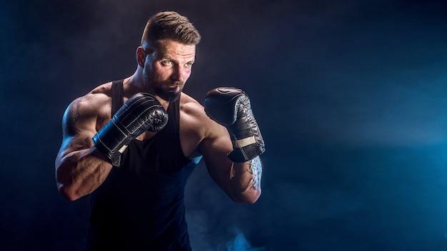 Боксер спортсмена борется на черной стене с тенью. копировать пространство. концепция спорта бокса.