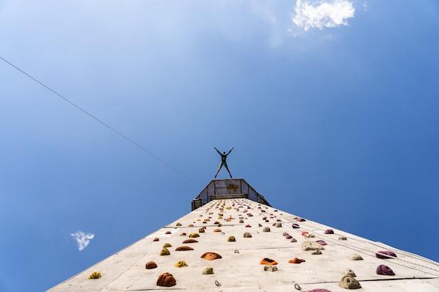 스포츠맨 산악인 훈련 야외 푸른 하늘, 인공 다채로운 암벽 등반