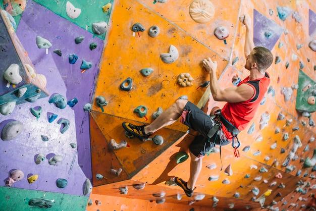 Sportsman climbing wall