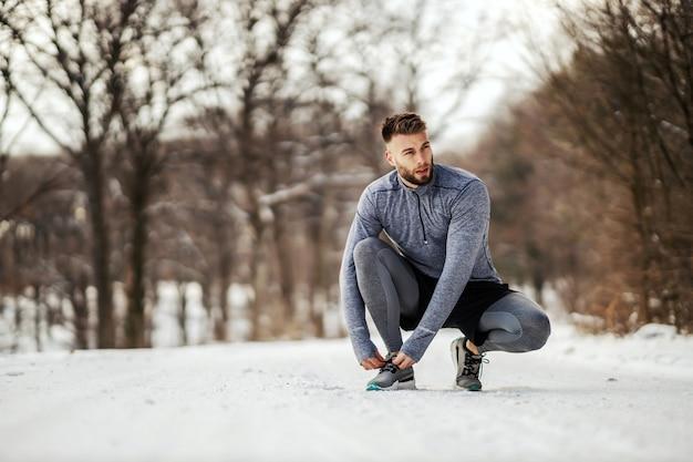 自然の中でトレイルにしゃがみ、雪の降る冬の日に靴ひもを結ぶスポーツマン。健康的なライフスタイル、スポーツウェア、雪の天気