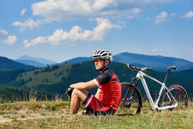 Sportsman cyclist in professional sportswear and helmet sitting near his bicycle on grassy roadside