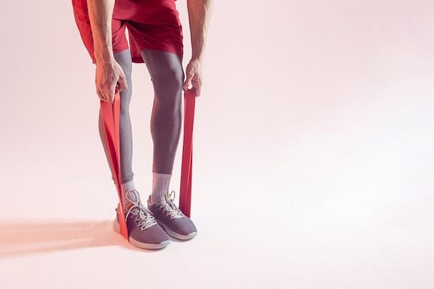Спортсмен делает упражнения с лентой сопротивления. обрезанное изображение человека носить спортивную одежду. изолированные на бежевом фоне. студийная съемка. копировать пространство