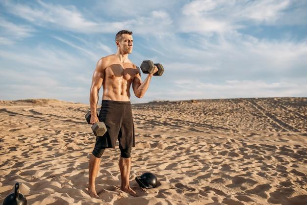 Спортсмен делает упражнения с весами в пустыне