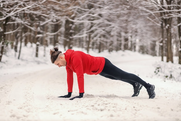 Sportsman doing push ups in forest at snowy winter day. healthy lifestyle, winter sport