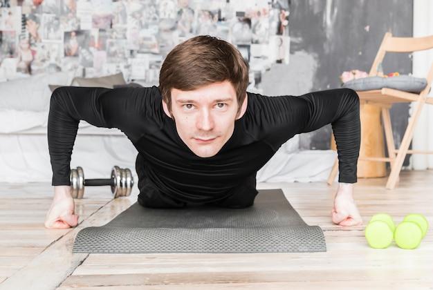 Sportsman doing push ups on mat