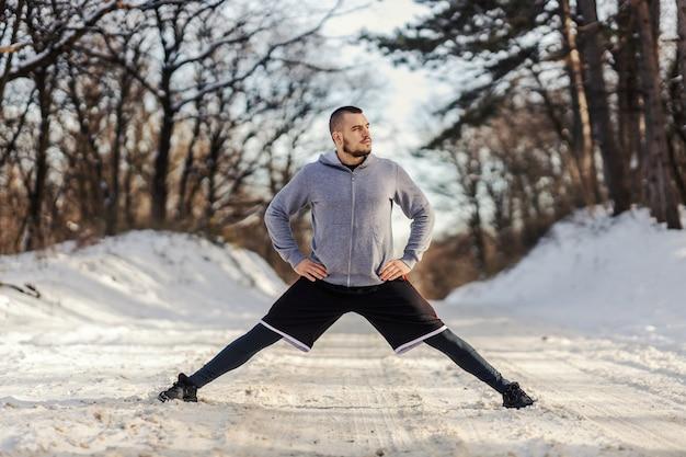 雪の降る冬の日に自然の中で立っている間、分割とストレッチ運動をしているスポーツマン